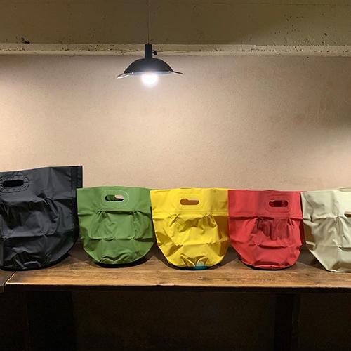 タープバッグ ターポリンという船の帆やお店のテントなどに使われる素材で作られたバッグです。表面は樹脂コーティングされており、耐水性・耐久性に優れているのが特徴。