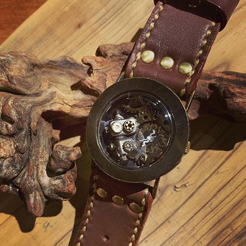 ロボットアクセサリー作家の小坂吉史氏と時計作家の秋友清孝氏がコラボレーションして造りあげた手作り腕時計です。文字盤の中にロボットがいるの、わかりますか?
