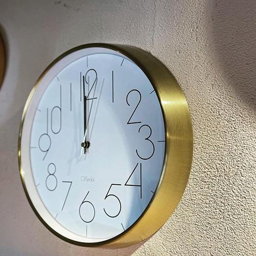 ゴールドのフレームと細いラインで描かれた数字がスタイリッシュな電波掛け時計。シンプルながら、大きな文字で時間を見やすくしました。